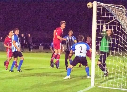 Newport's Jake Wright (in red) heads over the Cowes bar in their pulsating Wessex League Cup tie.  Photos: Simon Dear
