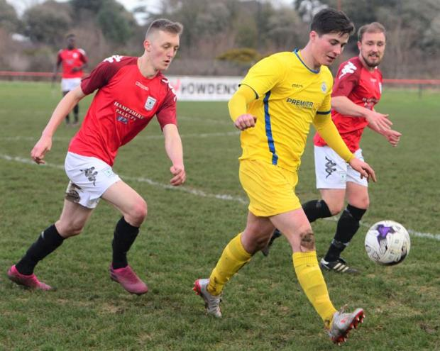 Isle of Wight County Press: Newport goalscorer Jordan Brown (in yellow) in possession against Hythe and Dibden at Beatrice Avenue, East Cowes.