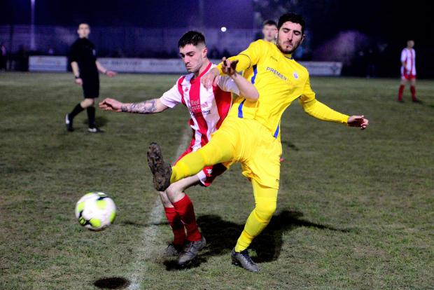 Isle of Wight County Press: East Cowes Vics forward, Brandon Hayward (in red) in a tussle with Newport's Spike Pearce.