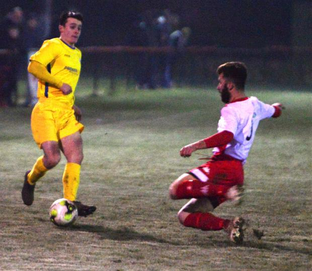 Isle of Wight County Press: Vics defender Liam Newbold (in red) tackles Newport full back, Ryan Hughes.