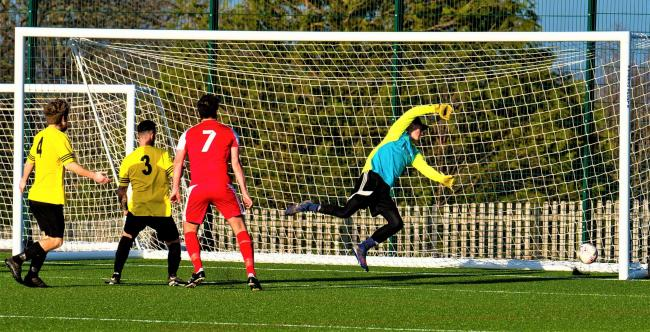 Brading Town's James Phipps (in red) scoring the winner with a great header past the hapless Whitecroft and Barton Sports keeper, Gareth True.