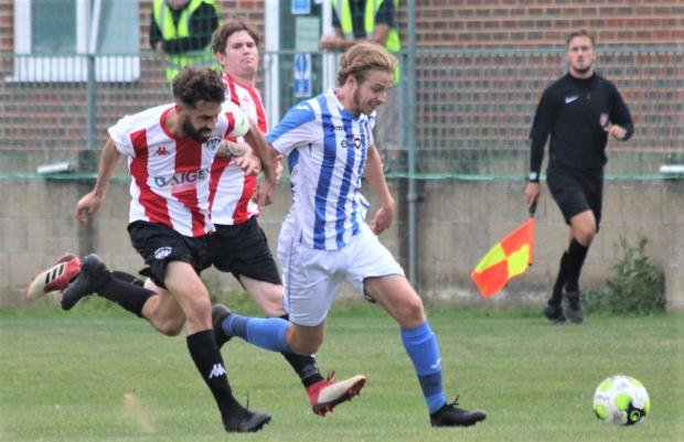 Isle of Wight County Press: Cowes winger Fin Phillips (in blue) taking on a Devizes defender.
