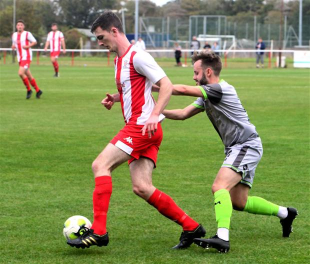 Isle of Wight County Press: Vics defender Oliver west brings the ball away from danger.